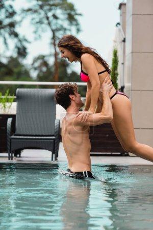 Photo pour Homme musclé debout dans la piscine tout en tenant dans les bras fille en maillot de bain - image libre de droit