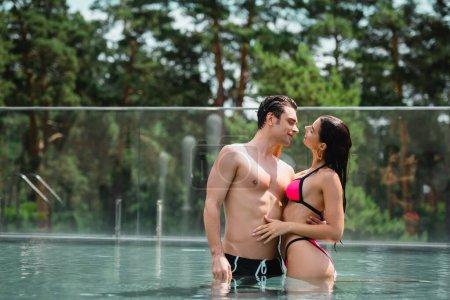Photo pour Homme musclé étreignant et regardant fille en maillot de bain debout dans la piscine - image libre de droit