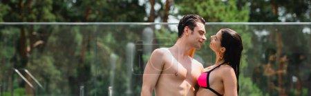panoramiczna koncepcja muskularnego mężczyzny przytulającego i patrzącego na dziewczynę w strojach kąpielowych