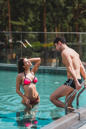 handsome man standing on pool ladder and looking at sexy woman in swimsuit