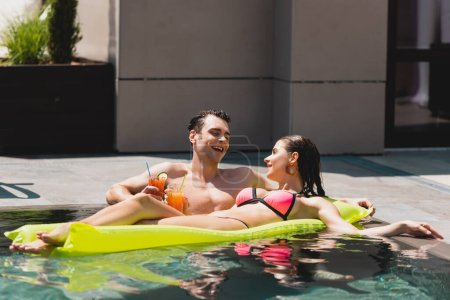 Photo for Happy woman lying on inflatable mattress near cheerful man holding cocktail in pool - Royalty Free Image