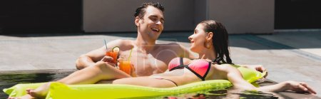 Photo for Panoramic crop of happy woman lying on inflatable mattress near cheerful man holding cocktail in pool - Royalty Free Image