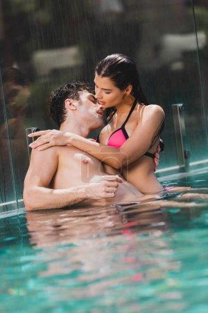 Photo pour Homme sexy étreinte avec fille humide dans la piscine - image libre de droit