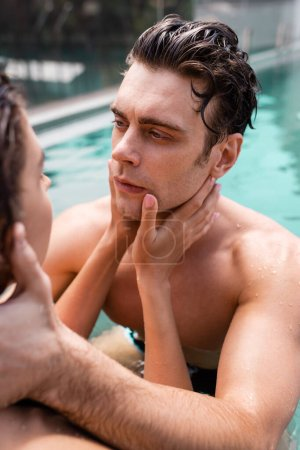 selective focus of woman touching shirtless and wet man in swimming pool