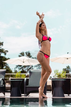 Photo for Attractive woman in swimsuit standing with hands above head near swimming pool - Royalty Free Image