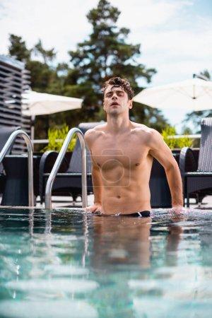 foyer sélectif de l'homme sexy et musclé regardant la caméra dans la piscine