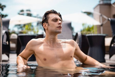 shirtless and sexy man looking away in swimming pool