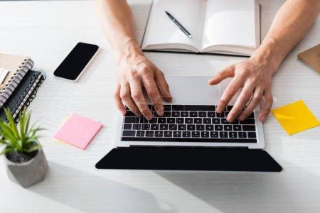 Photo pour Vue du dessus de l'homme tapant sur ordinateur portable avec écran vierge avec papeterie et smartphone sur la table à la maison, gagnant concept en ligne - image libre de droit