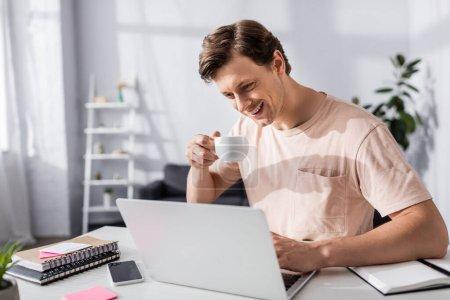 Photo pour Homme souriant regardant l'écran d'ordinateur portable et tenant tasse près de la table avec papeterie à la maison, gagnant concept en ligne - image libre de droit