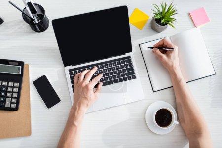 Photo pour Vue du dessus de l'homme dactylographiant sur l'ordinateur portable et écrivant sur l'ordinateur portable près du téléphone portable et de la papeterie sur la table, gagnant le concept en ligne - image libre de droit