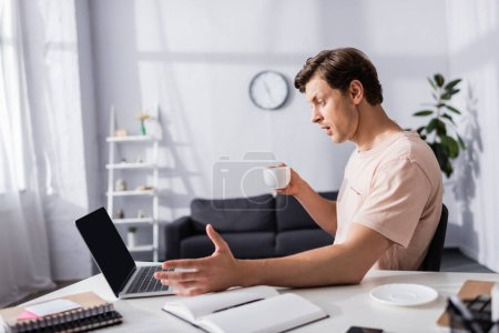 Photo pour Concentration sélective de pigiste surpris regardant l'écran d'ordinateur portable tout en tenant la tasse à la maison, gagnant concept en ligne - image libre de droit