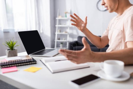 Photo for Cropped view of shocked freelancer sitting near laptop and stationery on table at home, concept of earning online - Royalty Free Image