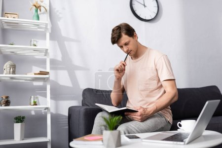 Photo for Selective focus of pensive freelancer holding notebook and pen near gadgets and coffee on coffee table, concept of earning online - Royalty Free Image