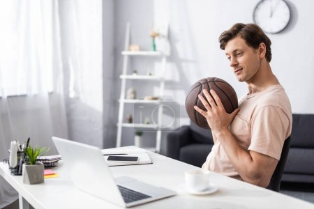 Photo for Selective focus of handsome man holding basketball near laptop and stationery on table at home, concept of earning online - Royalty Free Image