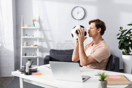 Photo for Selective focus of man kissing football while sitting near laptop and stationery on table at home, concept of earning online - Royalty Free Image