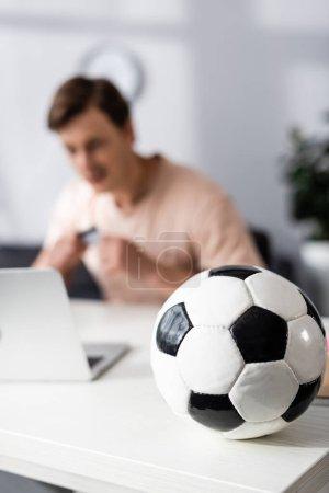 Photo pour Concentration sélective du football sur la table et l'homme assis près de l'ordinateur portable à la maison, concept de gagner en ligne - image libre de droit