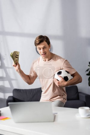 Photo for Selective focus of excited man holding cash and football near laptop on table at home, concept of earning online - Royalty Free Image