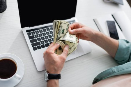 Photo for Cropped view of man holding dollar banknotes near cup of coffee and gadgets with blank screens on table, earning online concept - Royalty Free Image