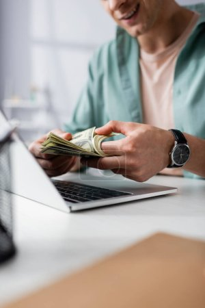 Cropped view of smiling man counting dollars near laptop on table at home, earning online concept