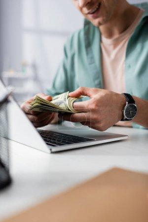 Vue recadrée d'un homme souriant comptant des dollars près d'un ordinateur portable sur la table à la maison, gagnant concept en ligne