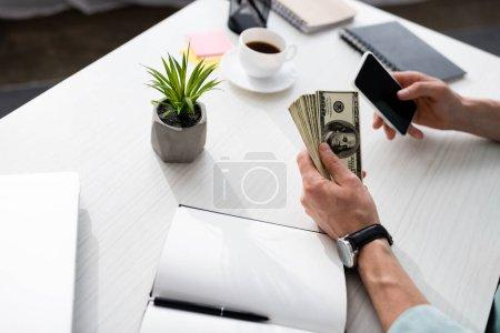 Photo pour Vue recadrée de l'homme tenant des dollars et en utilisant smartphone près ordinateur portable et café sur la table, gagner concept en ligne - image libre de droit