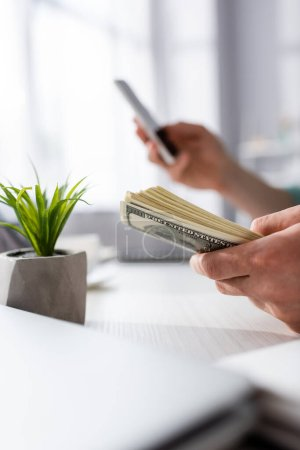 Cropped view of man holding money and using smartphone near plant on table at home, earning online concept