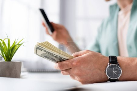 Photo for Cropped view of man holding dollars and using smartphone at home, earning online concept - Royalty Free Image