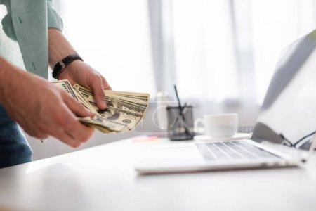 Foto de Enfoque selectivo del joven contando dólares cerca de la computadora portátil y la taza de café en la mesa, ganando concepto en línea - Imagen libre de derechos