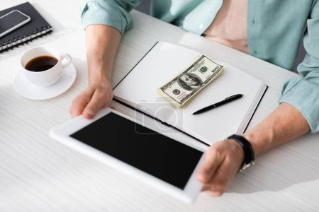 Cropped view of freelancer holding digital tablet near coffee and dollar banknotes on notebook at table, concept of earning online