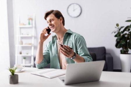 Selektiver Fokus des lächelnden Telearbeiters, der auf dem Smartphone neben Laptop und Notebook im Wohnzimmer spricht, Online-Konzept verdient