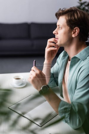 Photo for Selective focus of pensive freelancer holding pen near open notebook and cup of coffee at home - Royalty Free Image