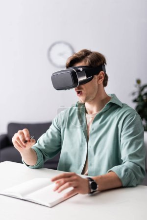 Photo for Selective focus of shocked man in vr headset holding pen near notebook on table - Royalty Free Image