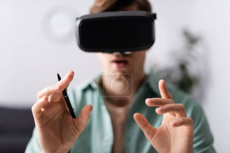 Photo for Selective focus of man in vr headset holding pen at home - Royalty Free Image