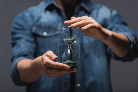 Cropped view of man holding hourglass with flowing sand isolated on grey, concept of time management