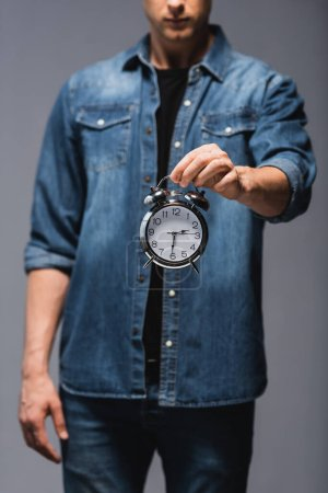 Cropped view o young man holding alarm clock isolated on grey, concept of time management