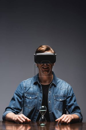 Selective focus of smiling man in vr headset sitting near hourglass on table on grey background, concept of time management