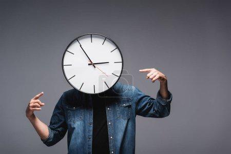 Photo pour Homme avec horloge près du visage pointant avec les doigts sur fond gris, concept de gestion du temps - image libre de droit