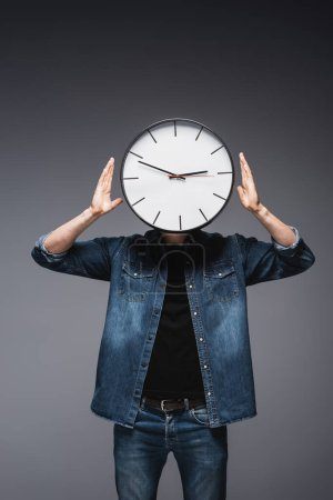 Young man in jeans jacket with clock on head on grey background, concept of time management