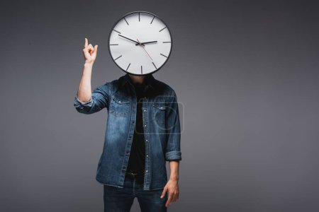 Photo for Man with clock near face pointing with fingers on grey background, concept of time management - Royalty Free Image