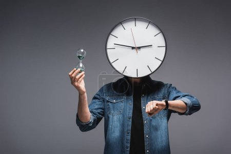Photo for Man with clock on head, wristwatch and hourglass on grey background, concept of time management - Royalty Free Image