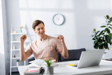 Photo for Positive freelancer showing yeah gesture near laptop and stationery on table at home, earning online concept - Royalty Free Image