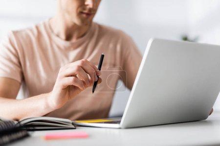 Freiberufler mit Stift und Laptop auf dem Tisch und Online-Konzept