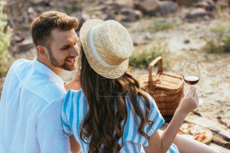 Photo pour Foyer sélectif de la fille dans le chapeau de paille tenant verre avec du vin rouge près petit ami heureux - image libre de droit