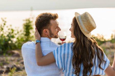 Photo pour Femme gaie en chapeau de paille touchant petit ami heureux tenant verre avec du vin rouge - image libre de droit