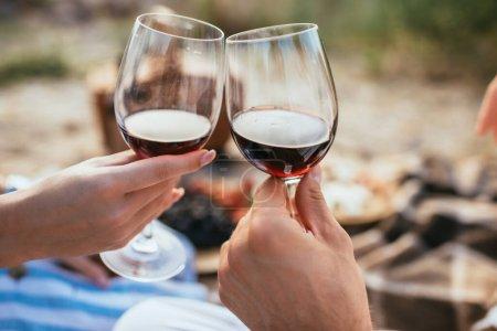 Photo pour Foyer sélectif de couple cliquetis verres avec vin rouge - image libre de droit