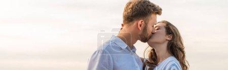 panoramic shot of bearded man kissing girlfriend outside