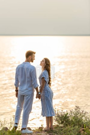 Photo for Handsome man and attractive woman holding hands near lake - Royalty Free Image
