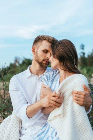 Photo pour Homme barbu étreignant belle petite amie enveloppée dans une couverture - image libre de droit