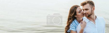 Photo pour En-tête de site Web de femme attrayante étreignant bel homme avec les yeux fermés près de la rivière - image libre de droit