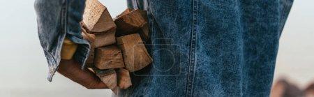 Photo pour Récolte panoramique de l'homme en veste de denim tenant du bois de chauffage - image libre de droit